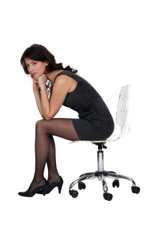 swivel: Brunette sitting on office chair Stock Photo