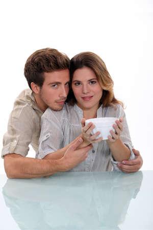 Couple holding empty bowl photo