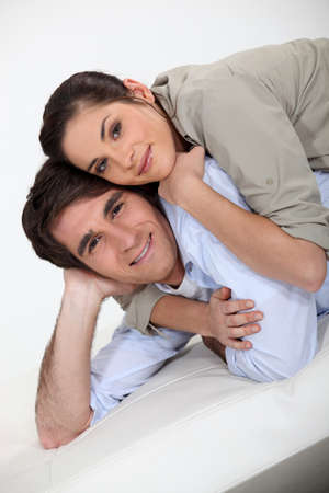 Portrait of a happy couple lying on a futon Stock Photo - 11445643