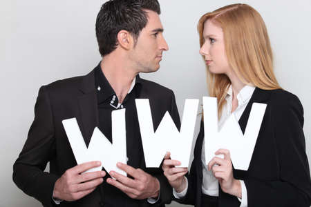 Man and woman in suit carrying www letters Stock Photo - 11138748
