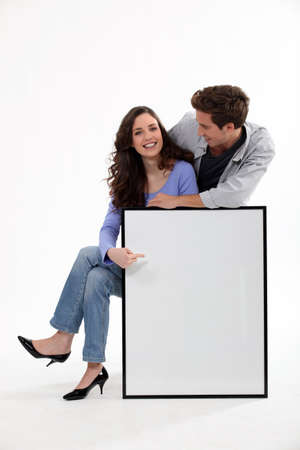 Couple with a picture frame left blank for your image photo
