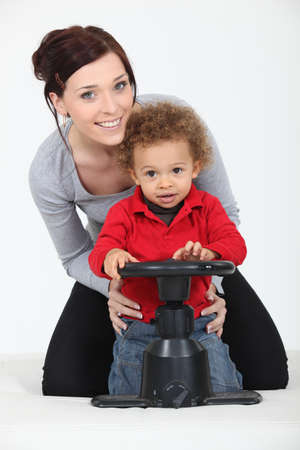 carer: Woman and child playing with a toy steering wheel