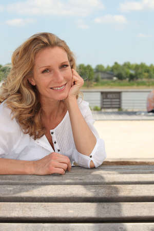 waterside: Portrait of a smiling summery woman sitting on a wooden bench