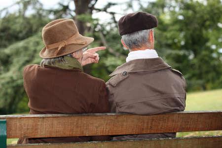 bench park: pareja de ancianos sentados en un banco del parque