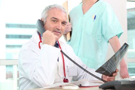 Doctor looking at x-ray whilst on the telephone Stock Photo - 11138742