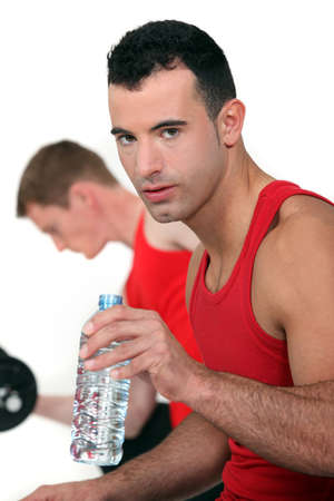 Athletic man with bottle of water photo