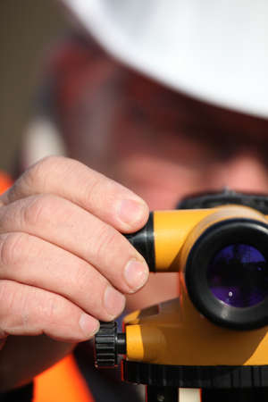 Civil engineer adjusting a theodolite photo