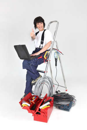 affix: Female electrician surrounded by tools