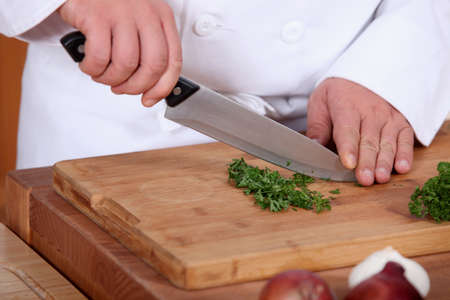 chopping board: hands of cook cutting parsley Stock Photo