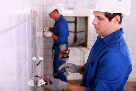 Electricians plumbing a bathroom photo