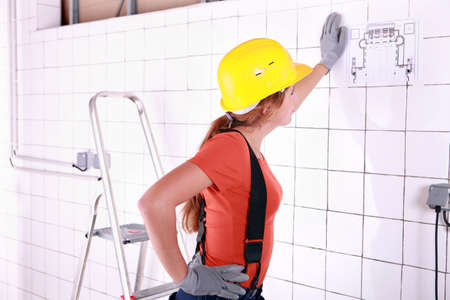 dwelling: craftswoman looking at an architectural plan Stock Photo