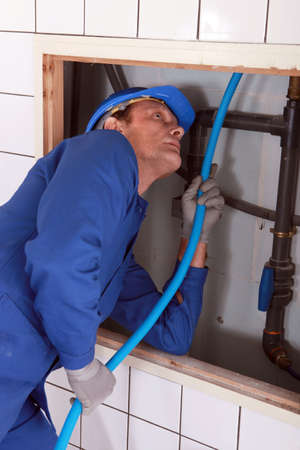 flexi: Plumber feeding blue pipe behind a tiled wall Stock Photo