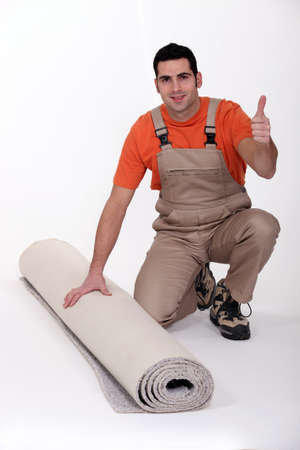 carpet and flooring: Man kneeling by rolled-up carpet