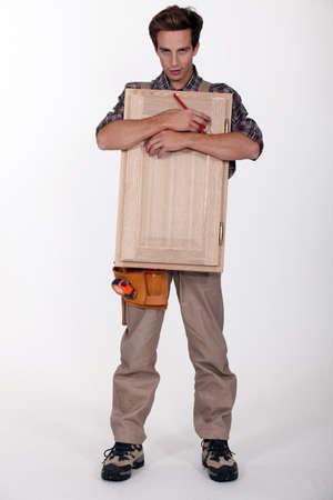 Carpenter with a cupboard door Stock Photo - 11717745