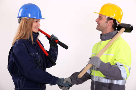 sledge hammer: two construction workers shaking hands Stock Photo