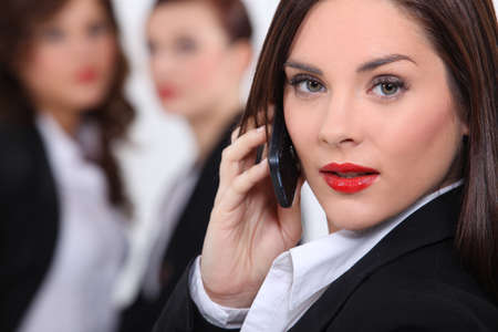 switchboard: Business woman making call colleagues in background