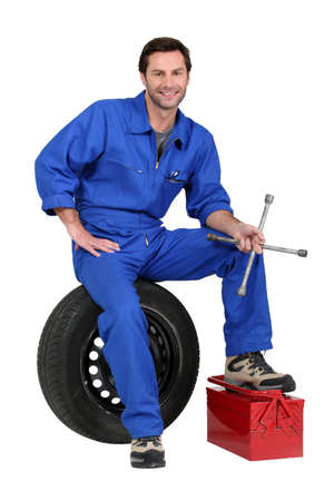 mechanic: Mechanic with tyre and tools Stock Photo