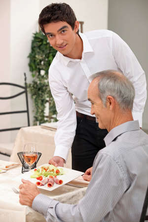 Young waiter serving an older customer photo