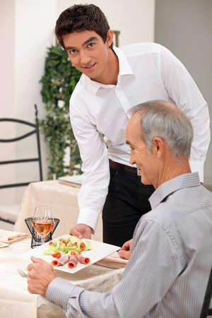 alcohol server: Young waiter serving an older customer