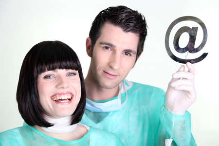 Doctors holding up the at symbol photo