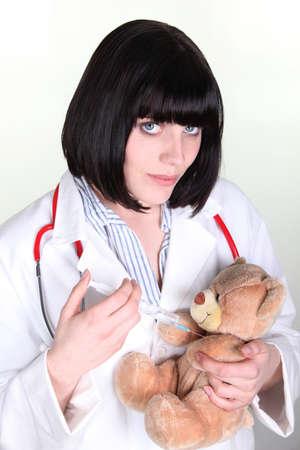 Female doctor injecting a teddy bear photo