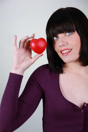 doctor holding gift: Young woman holding a small red heart