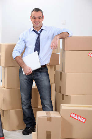 distributor: Courrier stood by stacked boxes