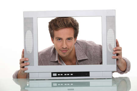 Young man smiling inside the frame of a TV set photo