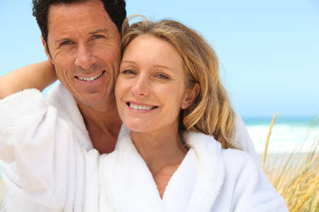 dressing gowns: Happy couple wearing dressing gowns at the beach