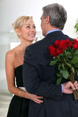 Un hombre encantador escondite rosas a sus espaldas Foto de archivo
