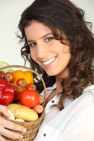 bright eyed: brunette with basket of vegetables Stock Photo