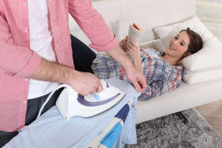 A man ironing while his girlfriend is reading on the sofa. photo