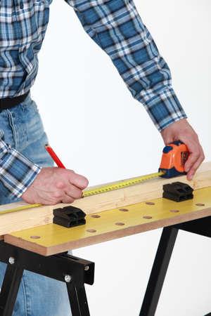 Carpenter measuring a plank photo