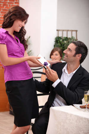 Woman giving a gift over dinner photo
