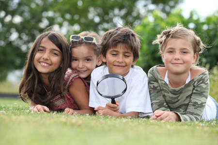 investigating: Kids playing with magnifying glass in park Stock Photo