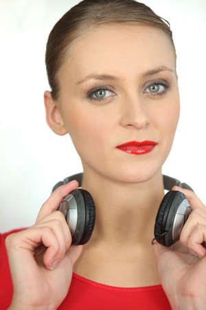 portable mp3 player: Woman in red with a pair of headphones Stock Photo