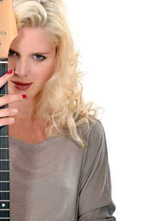 Beautiful woman peeking out from behind her guitar photo