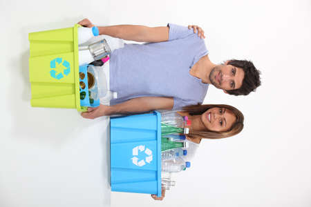 couple collecting plastics for recycling photo