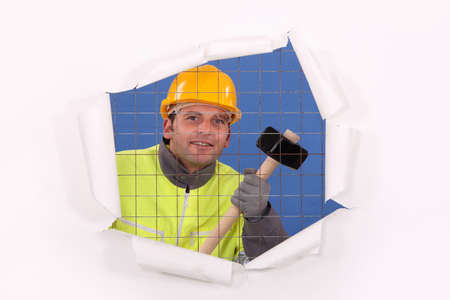 A man with a sledgehammer behind a wire netting. photo