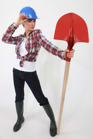 work boots: Woman dressed as a laborer posing with a shovel