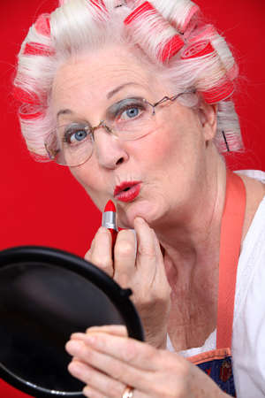 Grandmother with her hair in rollers applying lipstick photo