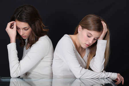 long faced: sisters sitting back to back after quarrel Stock Photo