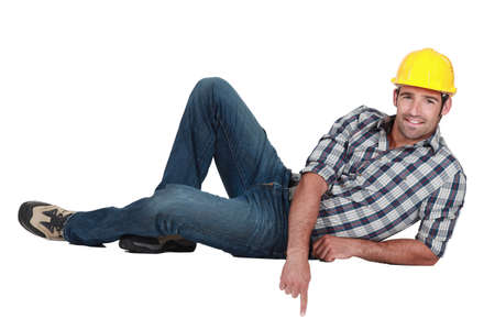 downwards: portrait of successful young craftsman pointing downwards Stock Photo