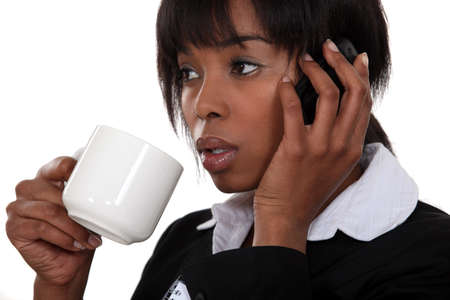 Afro-American businesswoman drinking coffee and talking on her cell Stock Photo - 11717712