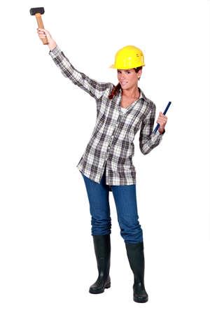 serrucho: Un trabajador de la construcción hembra con un martillo.