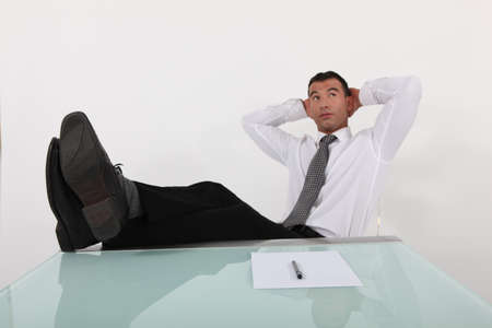 young businessman having a break with legs on table and arms behind head photo
