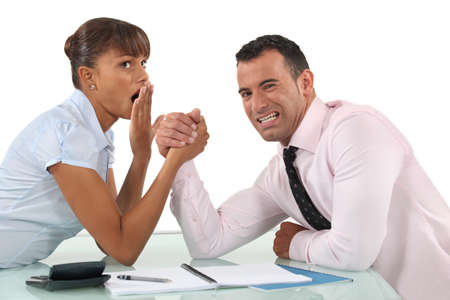 overpowered: A couple of businesspeople arm wrestling. Stock Photo