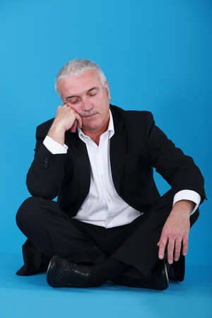 Man sitting cross-legged and falling asleep photo