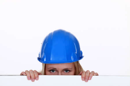 concealing: Tradeswoman peering over a low wall