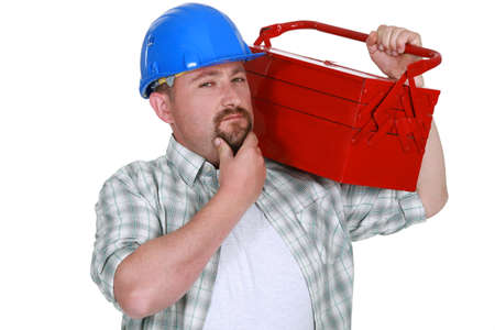 tradesmen: craftsman holding a tool box and touching his chin Stock Photo